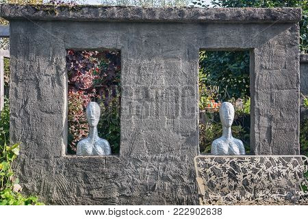 Apeltern, Netherlands, September 29, 2017: Two rectangular holes in the wall filled with two busts and in front an iron frog bench
