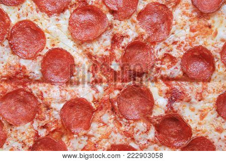 Pepperoni Pizza Close Up Background Full Frame Image. Sliced Hot Italian Pizza with Pepperoni Sausage, Cheese and Tomato Sauce Toppings. Fast Food Meal Closeup, Greasy Homemade Pizza Dish.
