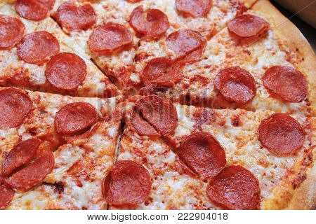 Pepperoni Hot Italian Pizza Close Up Image. Freshly Baked Traditional Recipe Pizza, Thin Pie with Pepperoni Sausage,  Cheese and Tomato Sauce Toppings. Pizza Isolated on Pizzeria Restaurant Table.