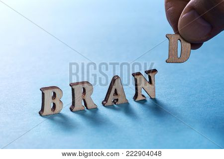 BRAMD from wooden letters on a blue background, a man's hand holds a letter D. Building a brand and bringing it to the market