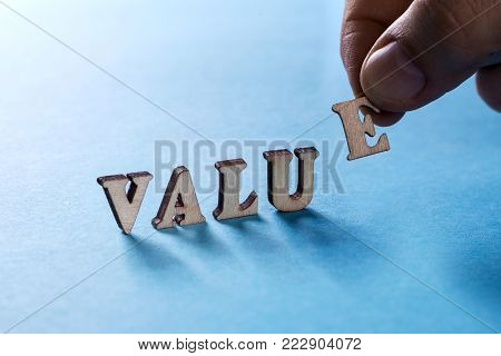 VALUE from wooden letters on a blue background, a man's hand holds a letter E