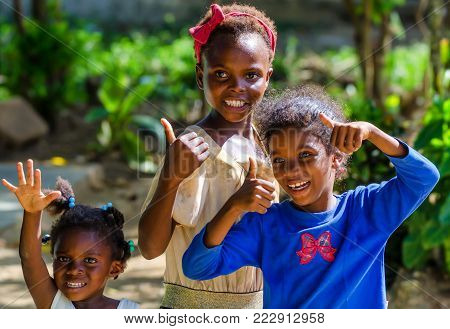 HIGUEY, DOMINICAN REPUBLIC - CIRCA NOVEMBER 2015: Three happy unidentified Dominican girls smiling and showing various gestures outdoors