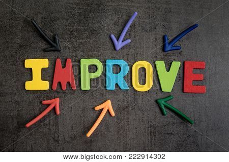 Self improvement concept by multiple arrow pointing to colorful alphabet IMPROVE at the center on dark black cement wall background.