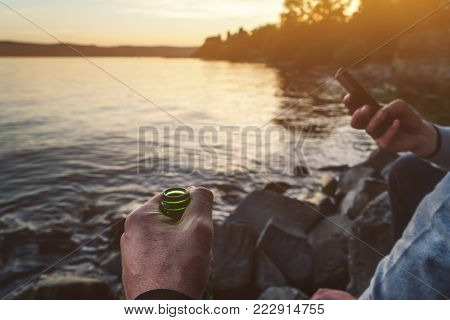 some people chill together on the shore and drink beer during sunset