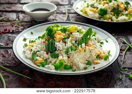 Fried rice with vegetables, broccoli, peas and eggs in a plate. healthy food.
