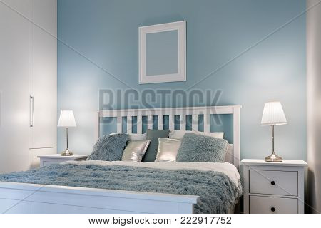 Stylish double bed in pastel colored bedroom