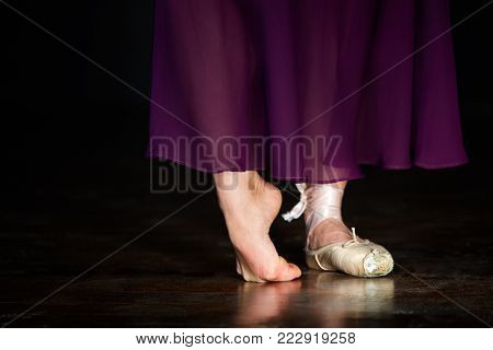 Elegant ballerina is posing in the studio on the dark background. She stands on the right toe and holds left leg on the floor. Girl wears one beige pointe shoe and long marsal satin skirt. Closeup. Horizontal. Her legs are reflected in the floor.