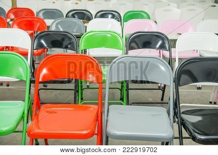 Rows of empty multicolor seats, chairs in auditorium, hall, classroom. Conference hall or seminar room. Selective focus