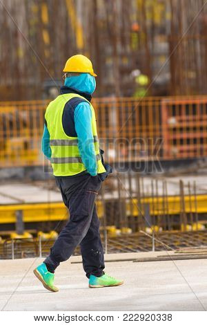 Twiddler is walking with hands in pockets through the  construction site
