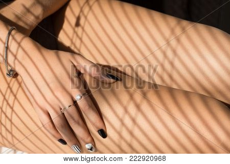 female feet in net tights under sunlight with blinds
