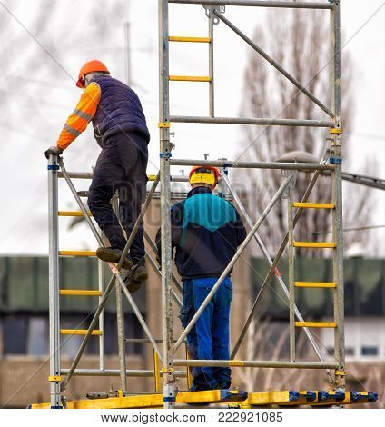 Two workers  build metal scaffolding on construction site