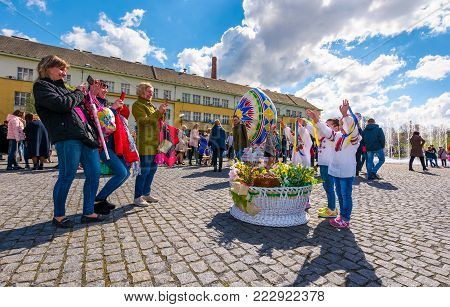 Uzhgorod, Ukraine - April 07, 2017: Celebrating Orthodox Easter in Uzhgorod on the Narodna square. women take photos of children near the big basket with flowers near huge egg on warm springtime day.