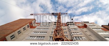 Facade of new multi-apartment high-rise apartment building. Construction of new modern multi-apartment residential complexes. Bottom panoramic view for new building and crane.