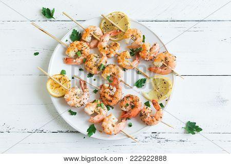 Grilled shrimp prawn skewers on white plate