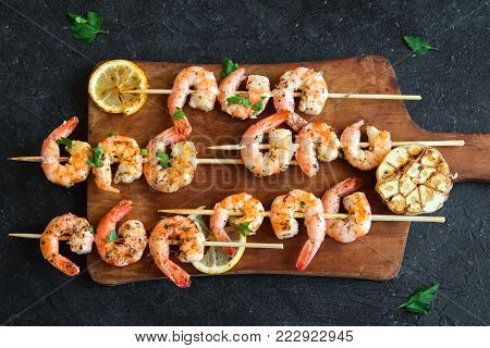 Grilled shrimp prawn skewers on black stone