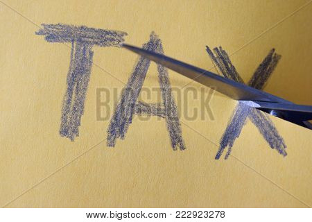 Scissors cut taxes on yellow paper - Tax Deduction
