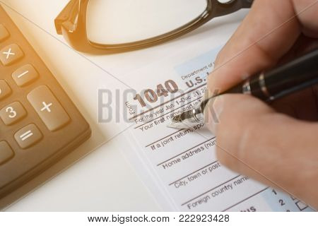 Man filling US tax form. tax form us business income office hand fill concept - closeup