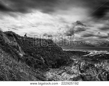 Lone figure sitting on clifftop looking out to sea, cliffs,black and white, shore-line, cloudy sky