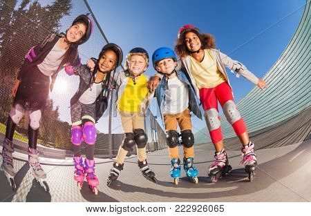 Portrait of five preteen boys and girls, happy roller-skaters in helmets, standing together in line at outdoors stadium