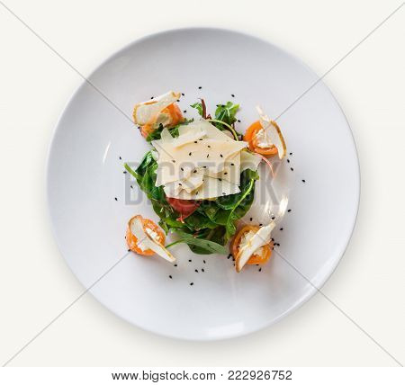 Restaurant dish on white plate at isolated background decorated with flowers, greens and tomatoes . Salad with spinach, arugula, cheese, salmon and baguette, top view