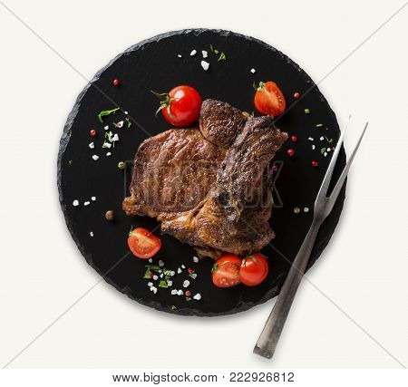 Rib eye steak and meat fork on black plate at white isolated background, cutout for restaurant menu, top view, copy space