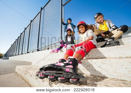Preteen boys and girls resting after roller skating, sitting on street stairs at sunny day