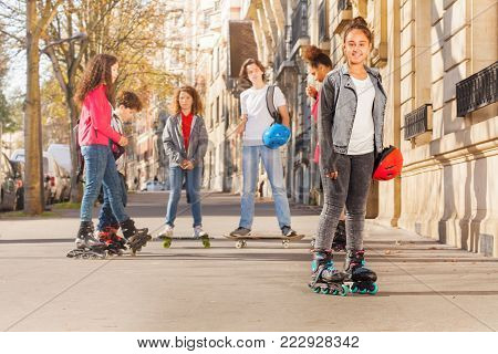 Happy teenage girl wearing roller skates standing in town with her friends