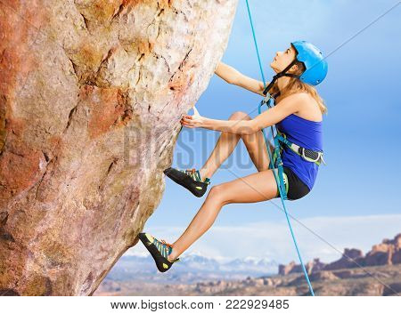 Side view portrait of female rock climber trying to reach the top of the mountains