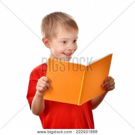 The boy is reading a book. A smart teenager. A boy in a red T-shirt. Happy childhood. Good mood.