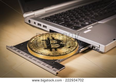 Physical giant bitcoin over a laptop's CD drive . Trading and mining concept of cryptocurrency