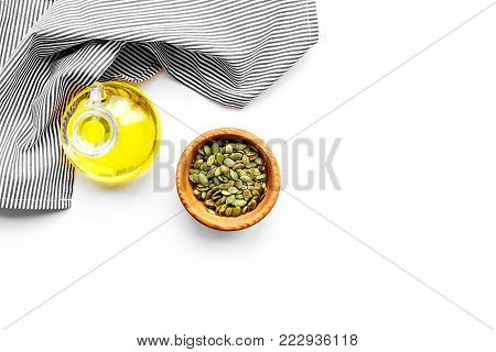 Use seed oil as cosmetics. pumpkin seed oil in jar near pumpkin seed in bowl on blue tablecloth on white background top view.
