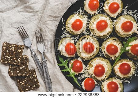 Snack with eggplant, cheese and cherry tomatoes supplied in a black plate. View from above.