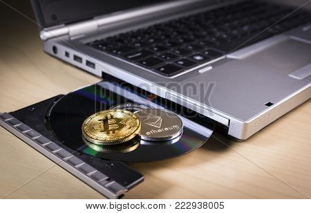 Physical bitcoin and ethereum over a laptop's CD drive . Trading and mining concept of cryptocurrency