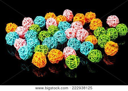 Multicolor rattan light balls on the black background. Creative decoration concept for Christmas celebration and Holiday.