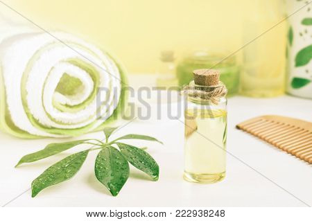 Bottle of aroma oil and towels, sunlit, yellow green tones, body and hair care organic cosmetic products.