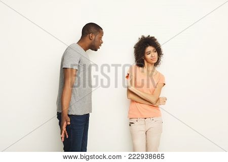 Black couple arguing. Angry african-american men shouting at his girlfriend at white studio background. Break up or divorce, family misunderstanding concept, copy space, isolated