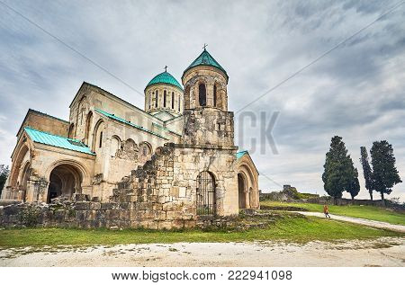Woman walking to the Chapel tower of Bagrati church at overcast sky in Kutaisi, Georgia
