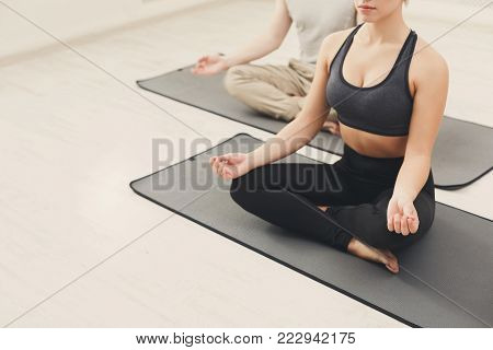 Young couple meditating together. Unrecognizable man and woman sitting near in lotus pose on mat, copy space