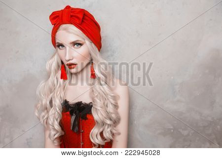 Young model on a gray background. Blonde model with a luxurious hairdo. Stylish model in retro dress. Model with natural make-up. Luxurious blonde model with beautiful long white hair and red lips in a red turban
