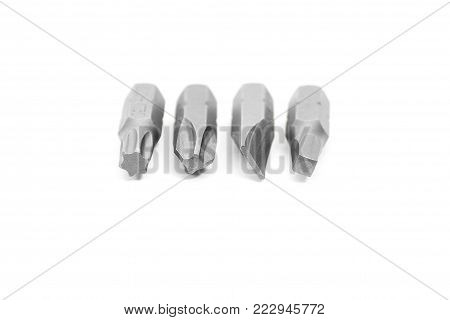 Set of 4 different interchangeable bits for a screwdriver head on a white background in shallow focus
