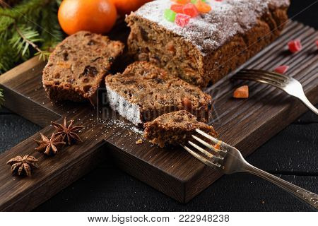 Slices of traditional English fruit cake with candied fruits served with clementines and star anise on oak board closeup
