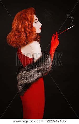 A model in stylish clothes. A stylish woman. Girl with a stylish hairstyle. Young stylish woman. Model in a stylish dress. Red-haired stylish woman with curly hair in red stylish dress and long gloves smoke on black background.