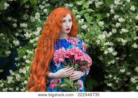 Fairy woman with pale skin and long red hair in peony dress. Fairy in the forest. Fairy in retro dress. Beautiful fairy from a fairy tale. A young fairy with a beautiful hairdo. Fairy on a fairytale spring background
