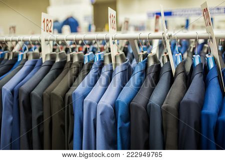 Hanger with men's jackets in the store. Classic style. Classic costume on a hanger. Blue suit in the store. Men's business suits hang in a row. Stylish men's suit