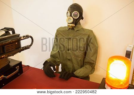 Modern military uniform. The military sits on the base. Good chemical protection. Conceptual photo with a military man. Chemical safety. Scary robot from recycled materials. A man sits in chemical protection and a gas mask
