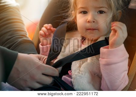 family, transport, road trip and people concept - Fastening security belt to toddler girl in car seat