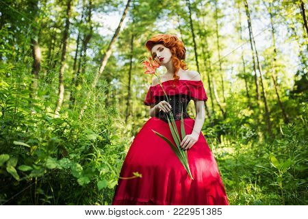 Young model on a summer background. Blonde model with a luxurious hairdo. Stylish model in retro dress. Model with natural make-up. Beautiful model in dress and in  on a green background. Model with red hair in a summer forest