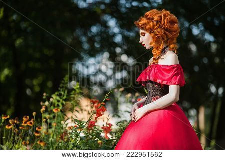 Elegant style of the girl. Retro style. Hairstyle in vintage style. Look of a girl in a renaissance style. Women's style. Beautiful red-haired girl in dress. A woman with red hair in a summer forest