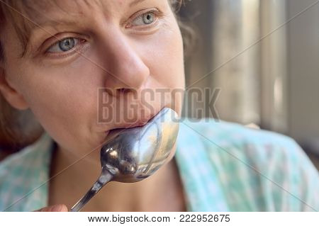 Closeup portrait of young woman licking spoon after tasty dish