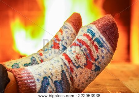 Man's Feet in lovely wool socks before cozy fireplace, in country house, winter vacation , horisontal, selective focus.